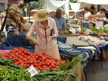 Lady shopping for tomatoes at a public market in Istanbul