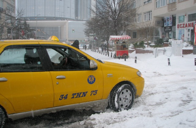 Istanbul Taksi trying to pass an intersection on a snowy road