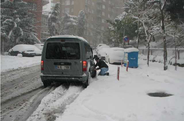 A man putting chain on a tire of his car to be able drive in snow.