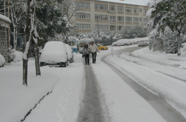 A couple walking in the middle of the road.