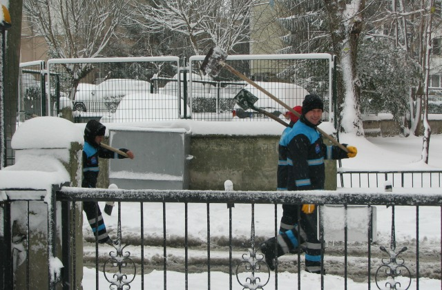 Municipality workers with shovels on their shoulders are all ready for cleaning up the snow.