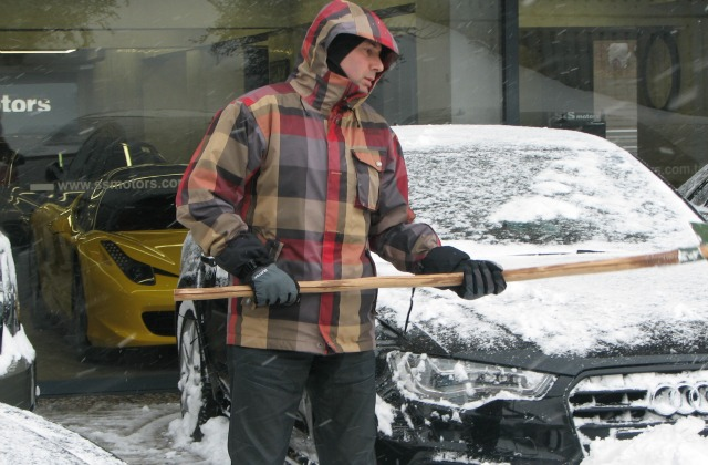 A man cleaning a car from snow.