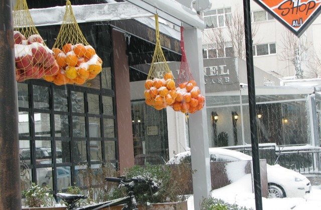 Oranges covered with snow at one of the shops which serves orange juice.